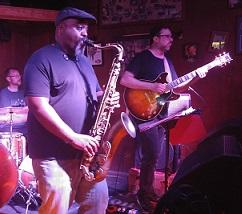 Heavy set black man in a cap playing the saxophone with other guys in a band onstage