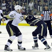 Two hockey players fighting on the ice with a ref looking on