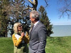Short blonde wtoman wearing a yellow coat and sunglasses talking and gesturing to a taller white man with gray hair and a gray suit outside by tree and a lake