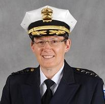 White woman in wire-rimmed glasses smiling in a pose with a police hat and uniform on