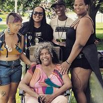 Four young black women posing behind an older black woman in a chair
