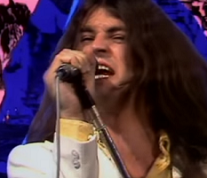 Long white man rock singer belting out a song into a mic with a blue and pink psychedelic background