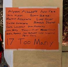 A sign on orange paper taped to a brown wall listing all the names of people killed in the recent Parkland Fla school shooting and the words 17 too many at the bottom