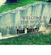 Sign that says Welcome to the Historic Near East Side and the words superimposed below Food Desert