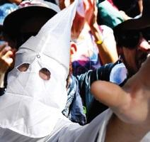 Someone in a Klan hood reaching out with his hand in a group of people
