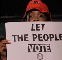Black person's face with a red hat on their head peering over a sign that they are holding that says Let The People Vote