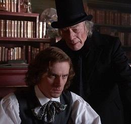 A man with chin length curly brown hair looking intense sitting down with old fashioned clothes from the 30s and an older gray haired man in black with a black top hat leaning over his shoulder saying something in his ear, bookshelves in the background