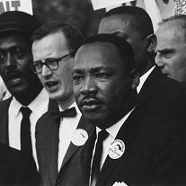 Black man in foreground, Martin Luther King Jr. surrounded by other men with sign above saying Now