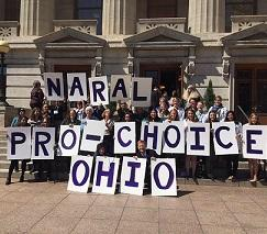 Big white capitol building with columns and turrets above windows in the background, lots of people posing in front holding placards each with a letter spelling out NARAL PRO-CHOICE OHIO