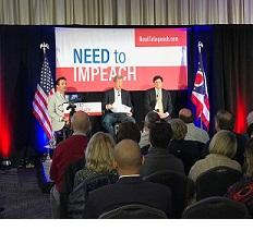 Red and white banner in the back between flags saying  Need to Impeach, three white men sitting facing the audience