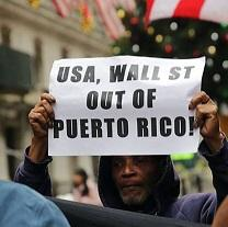 Black man holding a sign above his head saying USA, Wall St. Out of Puerto Rico