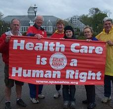 People holding a red sign that says Health Care is a Human Right