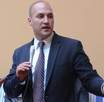 Baldish white man wearing a suit holding a microphone and talking