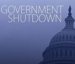 Blue background white letters saying Government Shutdown and the edge of the capitol building in DC