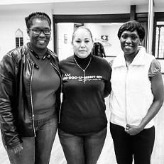 Black and white photo of three women, two black and one Latina smiling at the camera