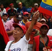 People of color outside at a rally one woman in front waving a red, blue and yellow striped flag