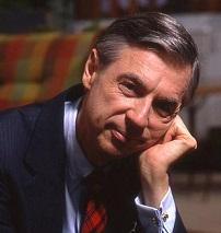 Older white man with dark and gray hair wearing a suit with his head resting on his hand