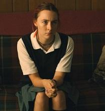Young white woman in a white blouse, vest and hair pulled back sitting on a couch with hands clasped looking irritated