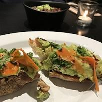 Two pieces of hard bread with green and orange foodstuff on them on a white plate with a bowl and glass on the table in the background