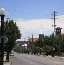 Street scene with a tower and trees and a lightpost and electricity poles