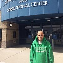 Bald older man wearing a green pullover sweatshirt that says Capital University standing in front of a building with glass doors and a glue curvy sign above that reads ...and correctional center