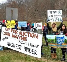 Lots of young people wearing coats outside near a forest at a fence with protest signs reading Up for Auction Our Wayne to the Highest Bidder