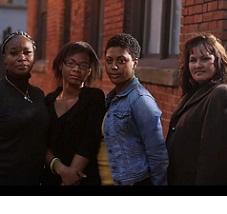 Three black women and a white woman standing outside looking very serious