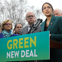 Sign saying Green New Deal with people behind it and young woman with glasses speaking