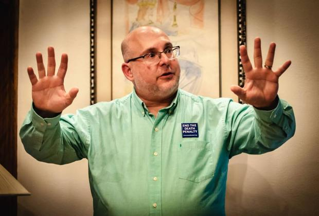 White middle aged guy with glasses holding his arms in the air with fingers spread on hands while he talks and wears an Abolish the Death Penalty button