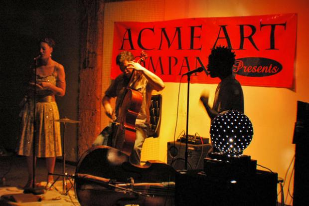 A red sign sayigng ACME ART on the wall behind silhouettes of musicians, a guy playing a bass fiddle, a person singing into a mic and a woman wearing a mid-length dress