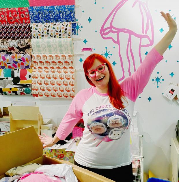 Woman with red hair and pink glasses holding up her hand like waving hello in a room with a lot of arts and crafts supplies