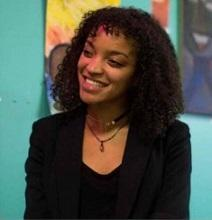 Young black woman smiling in a black suit against a colorful background