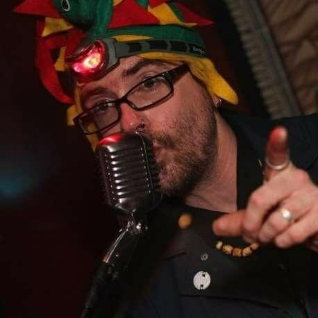Man with glasses in a colorful hat talking into a mic