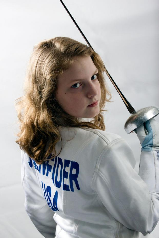 Very young blonde girl looking tough holding a sword