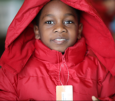 Young black child smiling and wearing a red winter coat with a hood