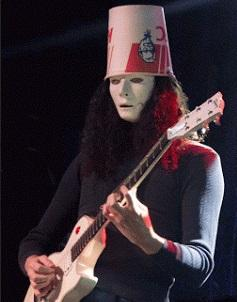 Guy playing guitar with Kentucky Fried chicken bucket on his head, he has white makeup like a mime