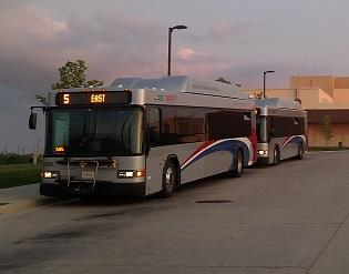 COTA bus, sllver bus with red white and blue curvy stripe on side driving in dusk