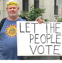 White man with yellow headband and blue T-Shirt with sun in the middle holding a sign that says Let the People Vote