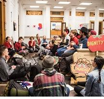 Dozens of kids sitting around an office with a tomato sign that says Dignity