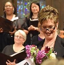 Three women in background holding songbooks and one in foreground smiling and holding flowers