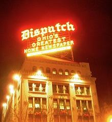 Bright yellow and red neon sign saying Dispatch Ohio's greatest homes newspaper above a big fancy building at night