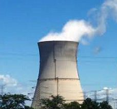 Big nuclear power plant smokestack with white smoke billowing out