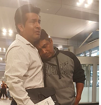 Two Latino men, one hugging the other, looking very sad
