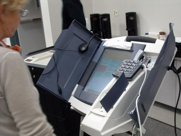 Older woman standing by an electronic voting machine
