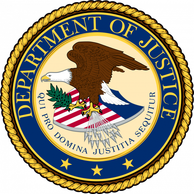 Round official seal with gold braided outside rim and blue around the circle that has words Department of Justice and an eagle facing left with wings held high on top of a shield with flag colors red, white and blue,