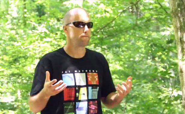 Young white man mostly bald holding his hands out in front of him standing in a forest