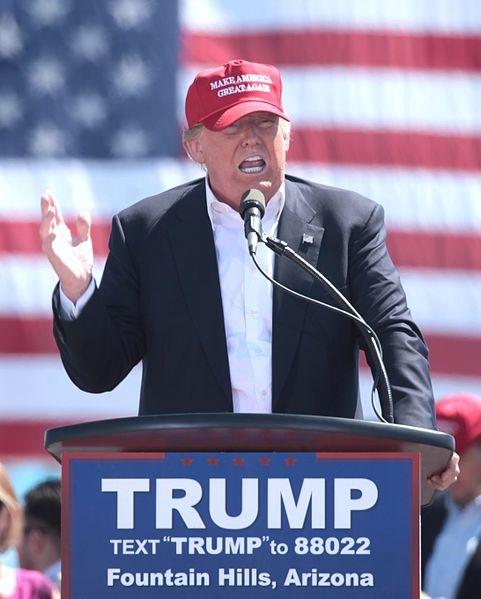 Trump in front of flag with red baseball cap on