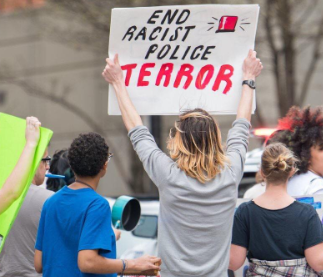 Woman holding sign saying End Racist Police Terror