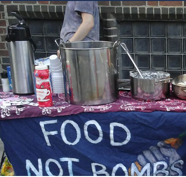Table with pots and pans and banner saying Food Not Bombs