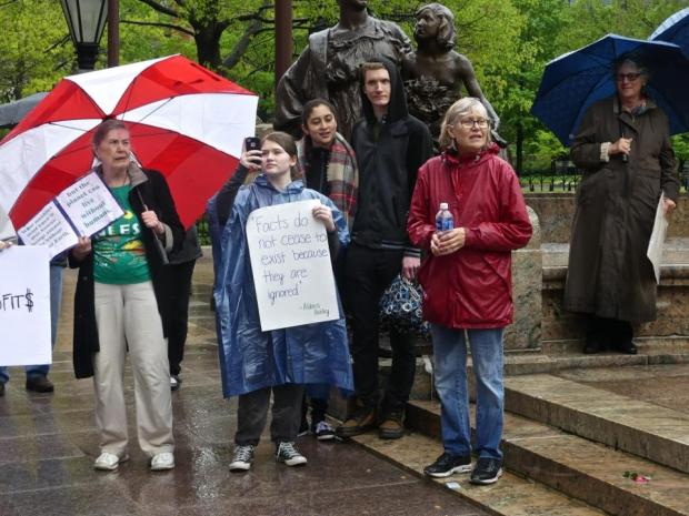 People in rain with signs touting the importance of facts